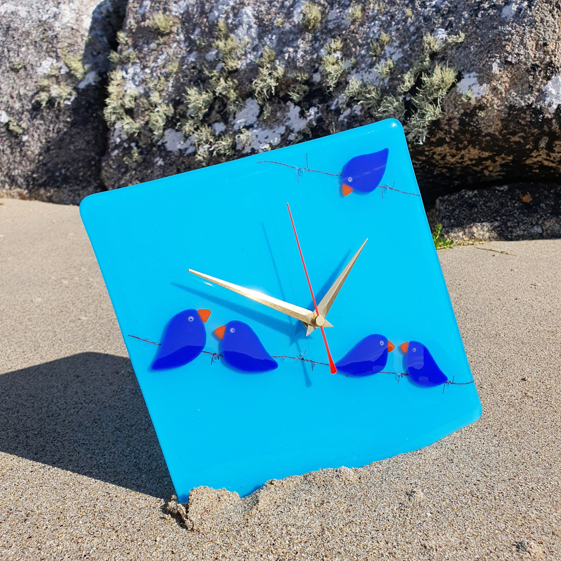 A fused glass clock featuring bright blue birds perched on barbed wire, set on a lighter blue background
