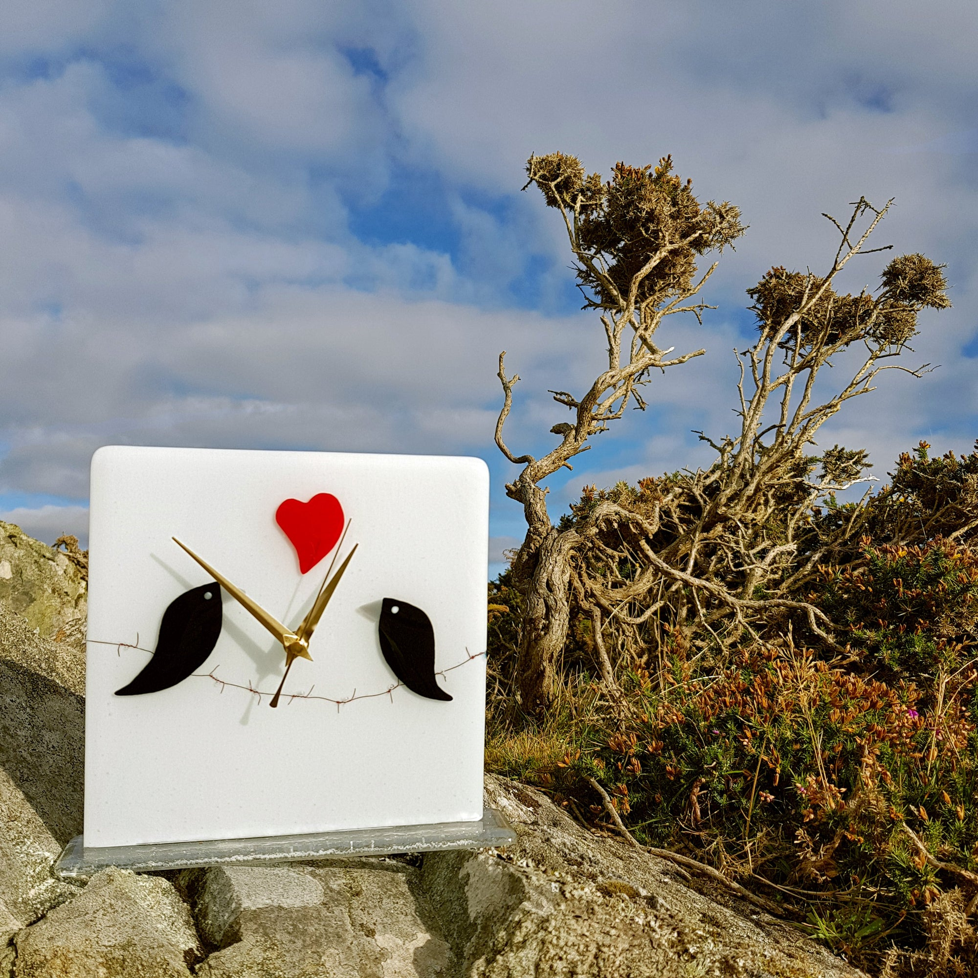 A freestanding white glass clock featuring two black birds in love, sitting on barbed wire, with a red heart motive. A lovely gift for someone special