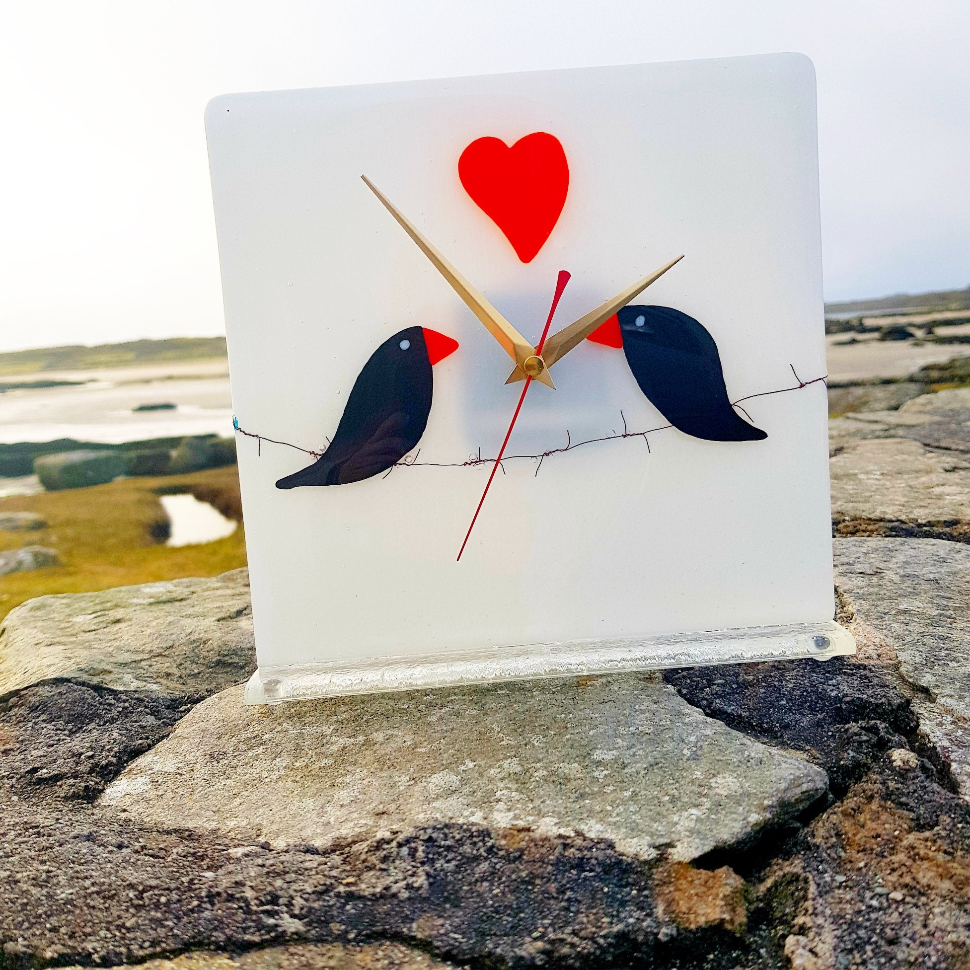 A freestanding white glass clock featuring two black birds in love, sitting on barbed wire, with an orange heart motive. A lovely gift for someone special