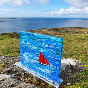 A freestanding glass sculpture featuring a Galway Hooker and the Wild Atlantic ocean,  handmade by Connemara Blue