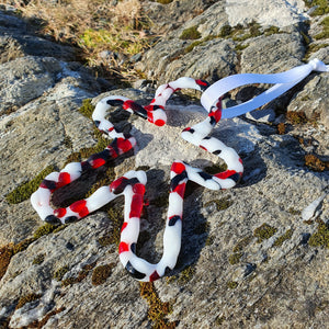 A fused glass tree decoration in the shape of a gingerbread man in red, black and white. Handmade by Connemara Blue