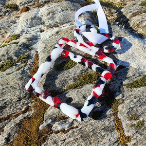 A fused glass tree decoration in the shape of a Christmas present in red, black and white. Handmade by Connemara Blue