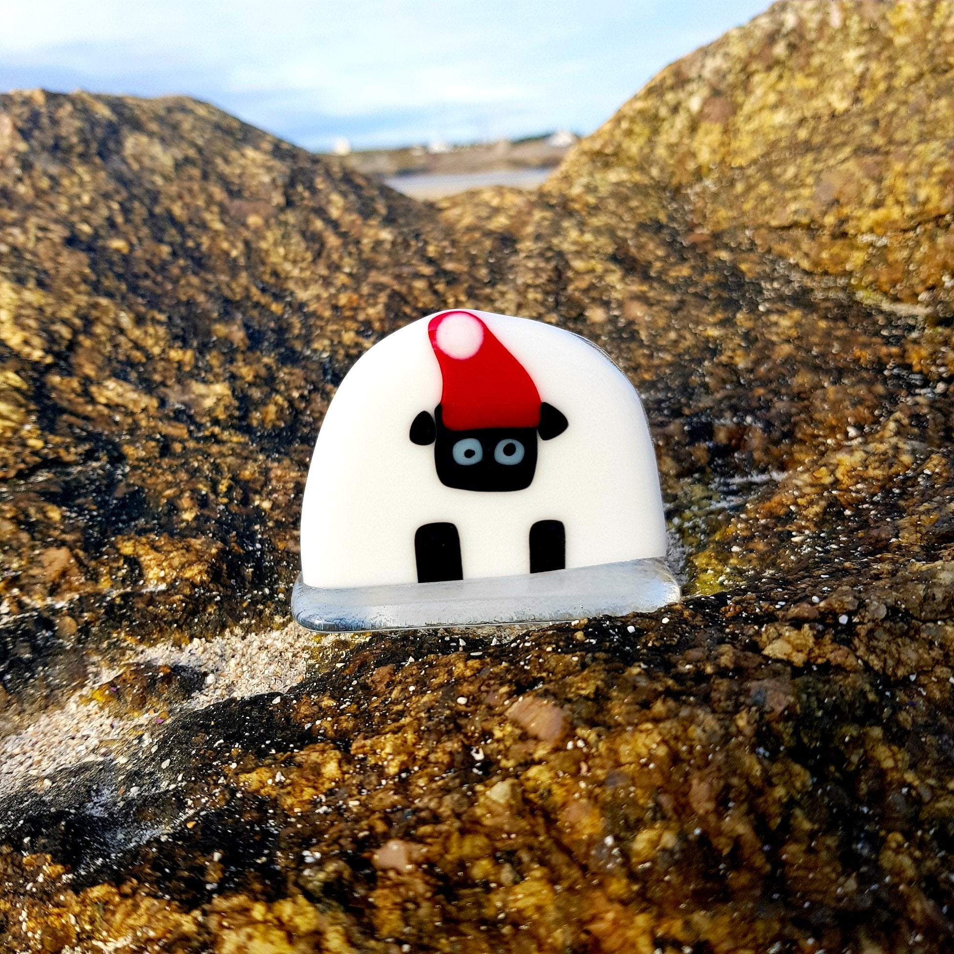 A freestanding fused glass Connemara sheep with a Santa hat, made by Connemara Blue