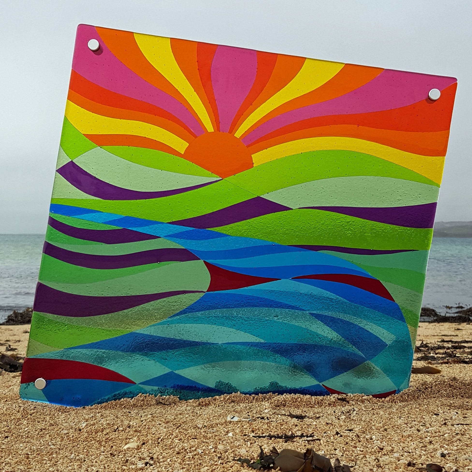 Fused glass wall panel featuring a sunrise over the mountains and lakes, made by Connemara Blue