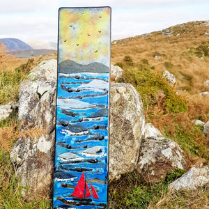 A fused glass wall panel showing a Galway Hooker on the Wild Atlantic Waves, made by Connemara Blue