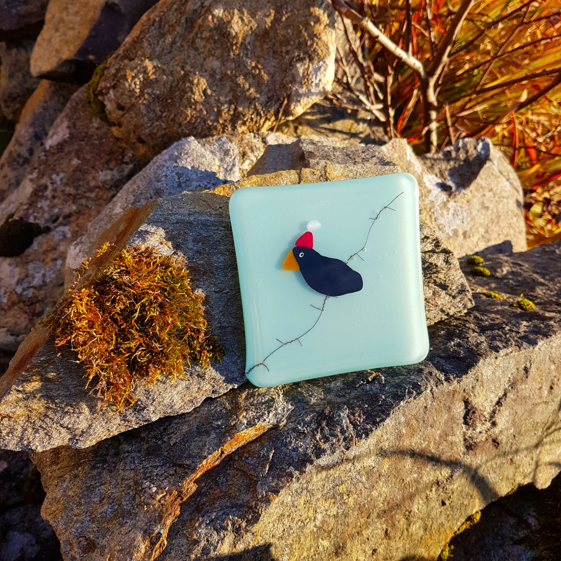 A charming and fun glass coaster featuring a blackbird with a santa hat sat on barbed wire. A great small gift idea, made by Connemara Blue