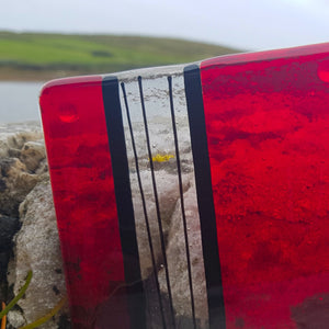 A striking glass coaster in red, transparent and black glass, featuring bold stripes. Unique tableware idea from Connemara Blue