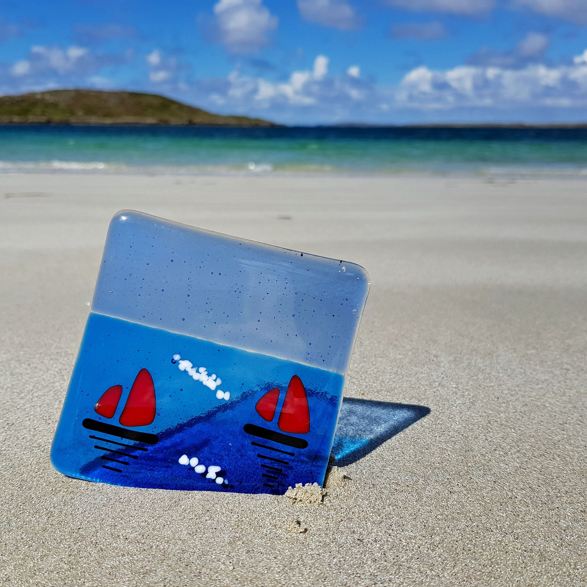 A glass coaster featuring two sailboats with bright red sails. An ideal small gift idea from Connemara Blue