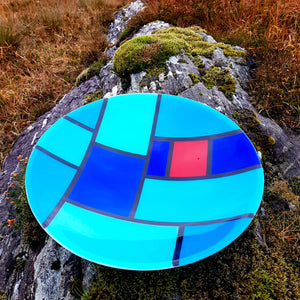 A stunning glass bowl featuring a geometric design of blues and red in the style of stained glass. An ideal gift for a collector, made by Connemara Blue