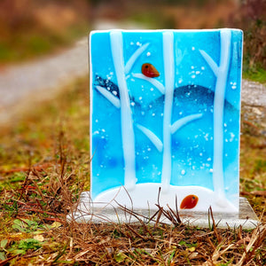 Glass freestanding candle shield featuring a snowy woodland scene on blue glass with two cute robins