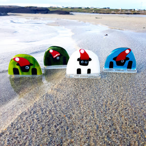 Four freestanding fused glass Connemara Sheep in Santa hats, made by Connemara Blue