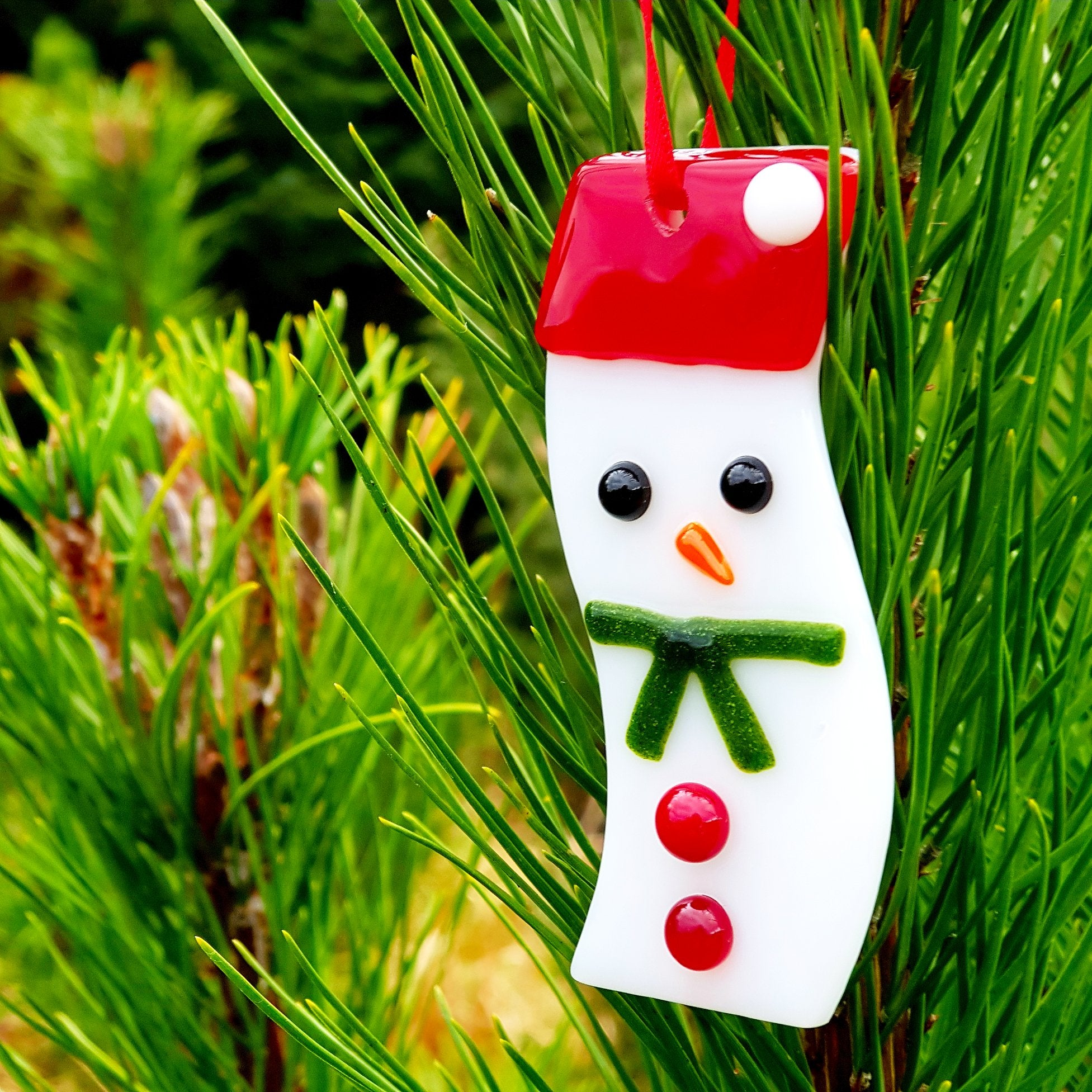 A hanging fused glass Christmas decoration in the shape of a wavy snowman, made by Connemara Blue