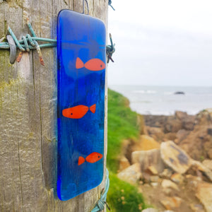 A bright glass suncatcher featuring orange fish in a vivid blue sea. A small gift idea with a difference, made by Connemara Blue