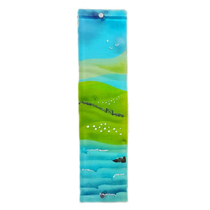Glass wall art featuring sea, fields, sheep, hills and blue skies; panel 1