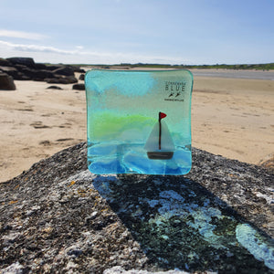 A fused glass tealight holder depicting a sailboat on the Atlantic Ocean