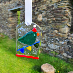 A fused glass decoration featuring a bird in a santa hat sitting on bunting in the snow. Handmade by Connemara Blue