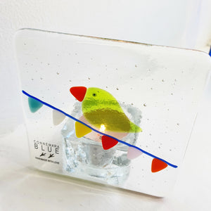 Fused glass tealight holder featuring a bright green bird on bunting, handmade by Connemara Blue