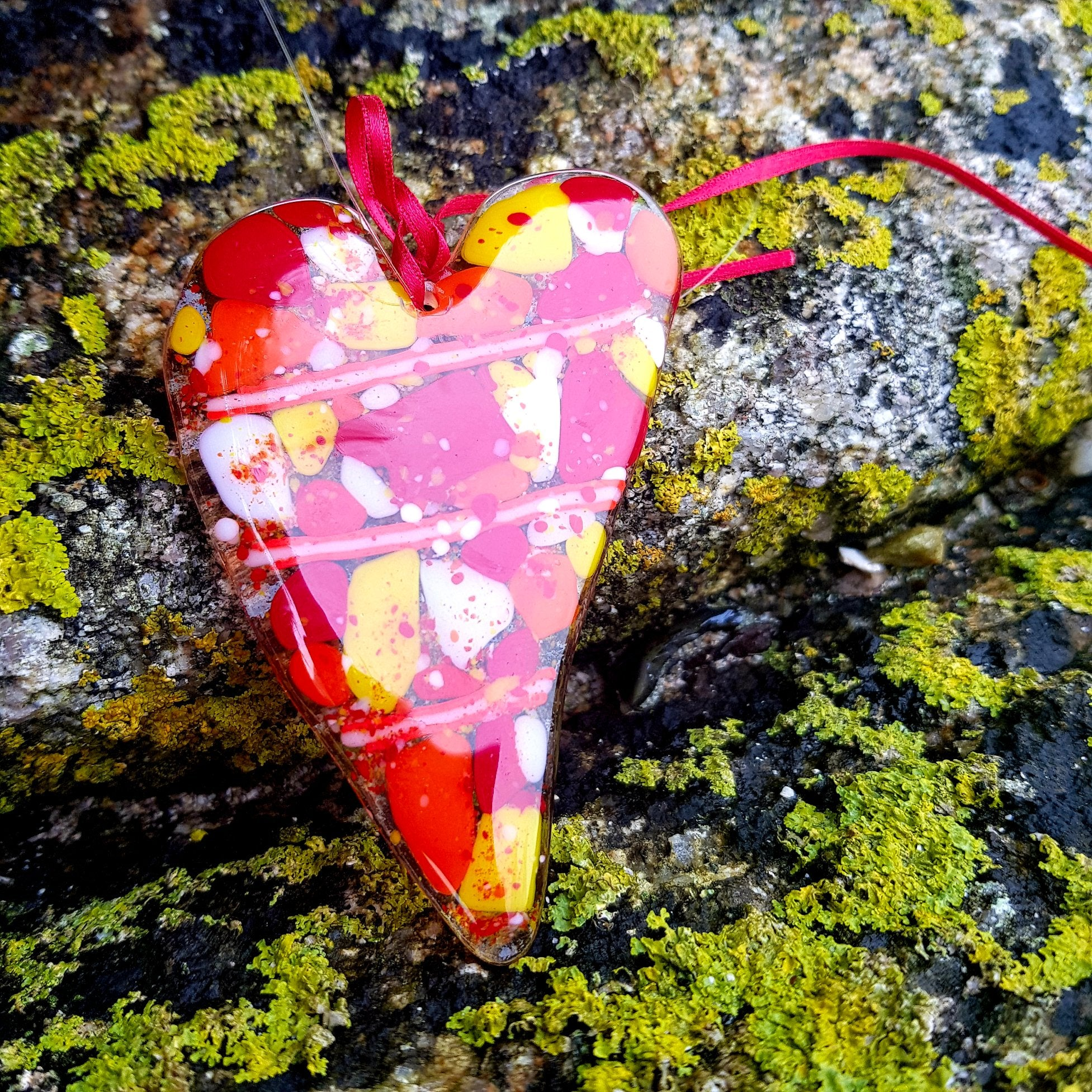A beautiful glass hanging decoration in the shape of a heart, made with red, yellow, orange and white glass