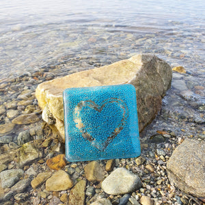 A fused glass coaster with bubbles and a heart, handmade by Connemara Blue