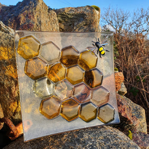 A square fused glass plate featuring a bee and honeycomb, perfect for carrying a honey pot, jar of jam, or a candle. Handmade by Connemara Blue
