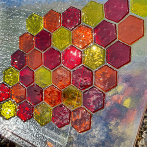 A square glass plate featuring a bold honeycomb design in red, yellow and orange, handmade by Connemara Blue