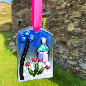 A fused glass hanging decoration based on a magical fairy garden theme, with shiny dichroic glass on a translucent powdered background. A lovely Christmas decoration or small gift idea, handmade by Connemara Blue