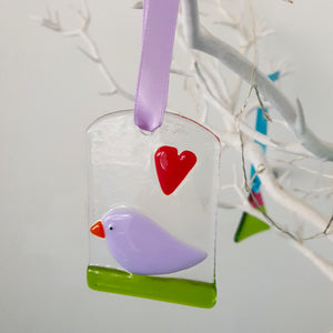 A fused glass hanging decoration featuring a red heart and a bird sitting on bright green grass , handmade by Connemara Blue