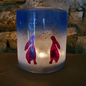 A fused glass candle shield featuring two moon gazing hares, handmade by Connemara Blue