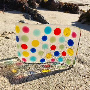 A fused  glass tea light shield featuring multicoloured bobbles on transparent glass