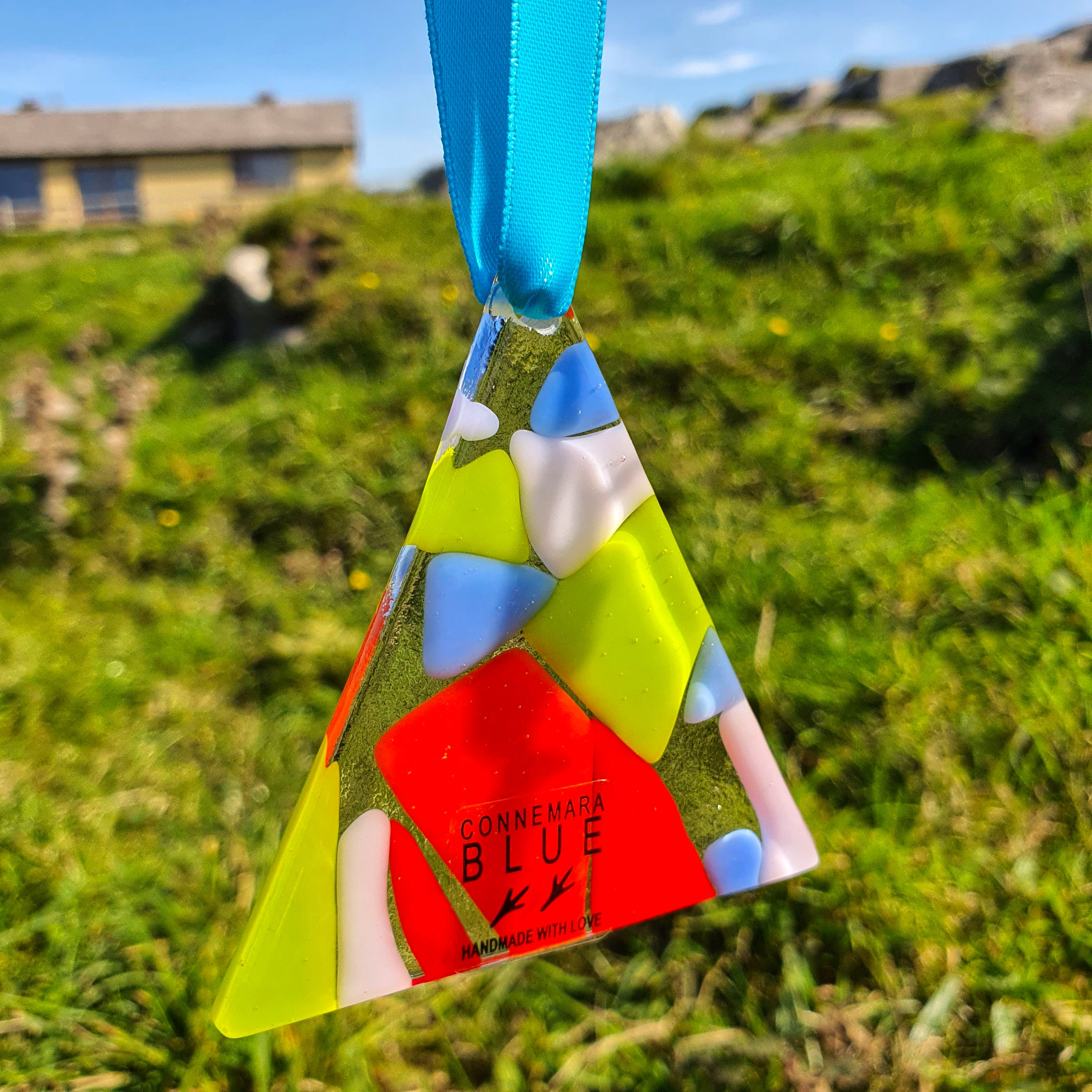 A multicoloured fused glass hanging decoration in a triangle shape, handmade by Connemara Blue