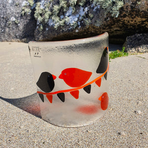 A fused glass candle shield featuring black and orange birds on black and orange bunting. A perfect gift for Halloween.