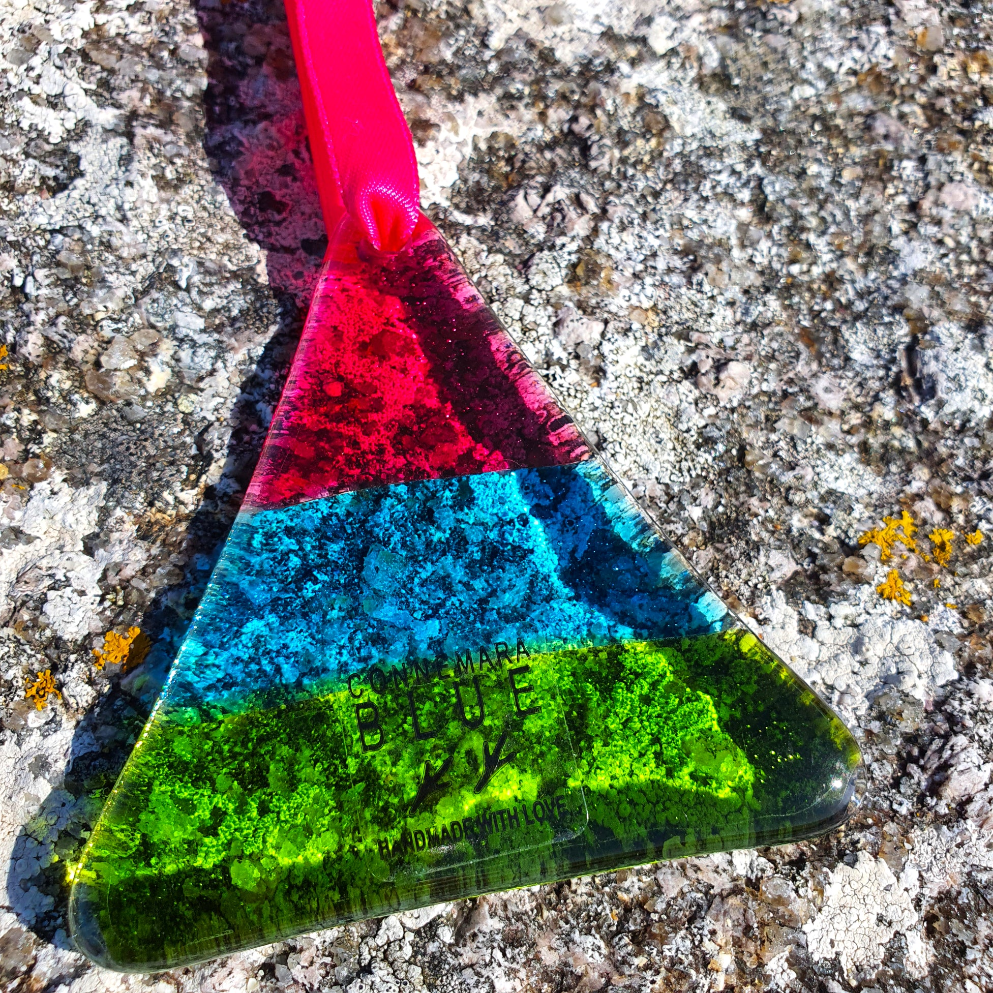 A fused glass hanging decoration in pink, blue and green, in the shape of a triangle