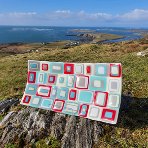 A fused glass rectangular plate crafted from stacked layers of red, grey, vanilla and blue, handmade by Connemara Blue
