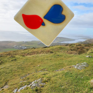 A fused glass coaster featuring a red bird and a blue heart on a vanilla background, handmade by Connemara Blue