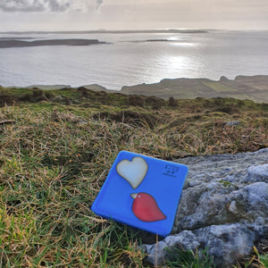A fused glass coaster featuring a red bird and a vanilla heart on a blue background, handmade by Connemara Blue