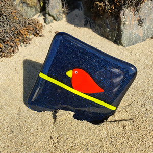 A fused glass coaster featuring a red bird on bunting, set on a sparkly blue background