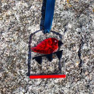 A unique fused glass hanging decoration featuring a bright red bird on black bunting. A great Halloween decoration or gift idea from Connemara Blue