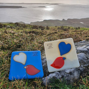 A pair of glass coasters in matching colours featuring a bird and a heart, handmade by Connemara Blue