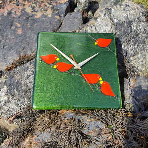 A fused glass clock featuring bright red birds perched on barbed wire, set on a sparkly green background