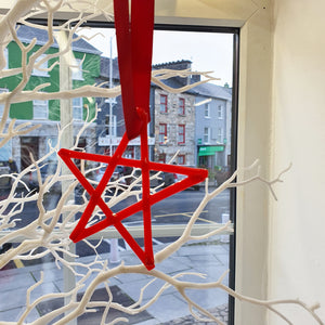 A red fused glass star decoration, handmade by Connemara Blue