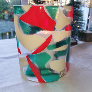 A fused glass candle shield in red, emerald green, and French vanilla, handmade by Connemara Blue