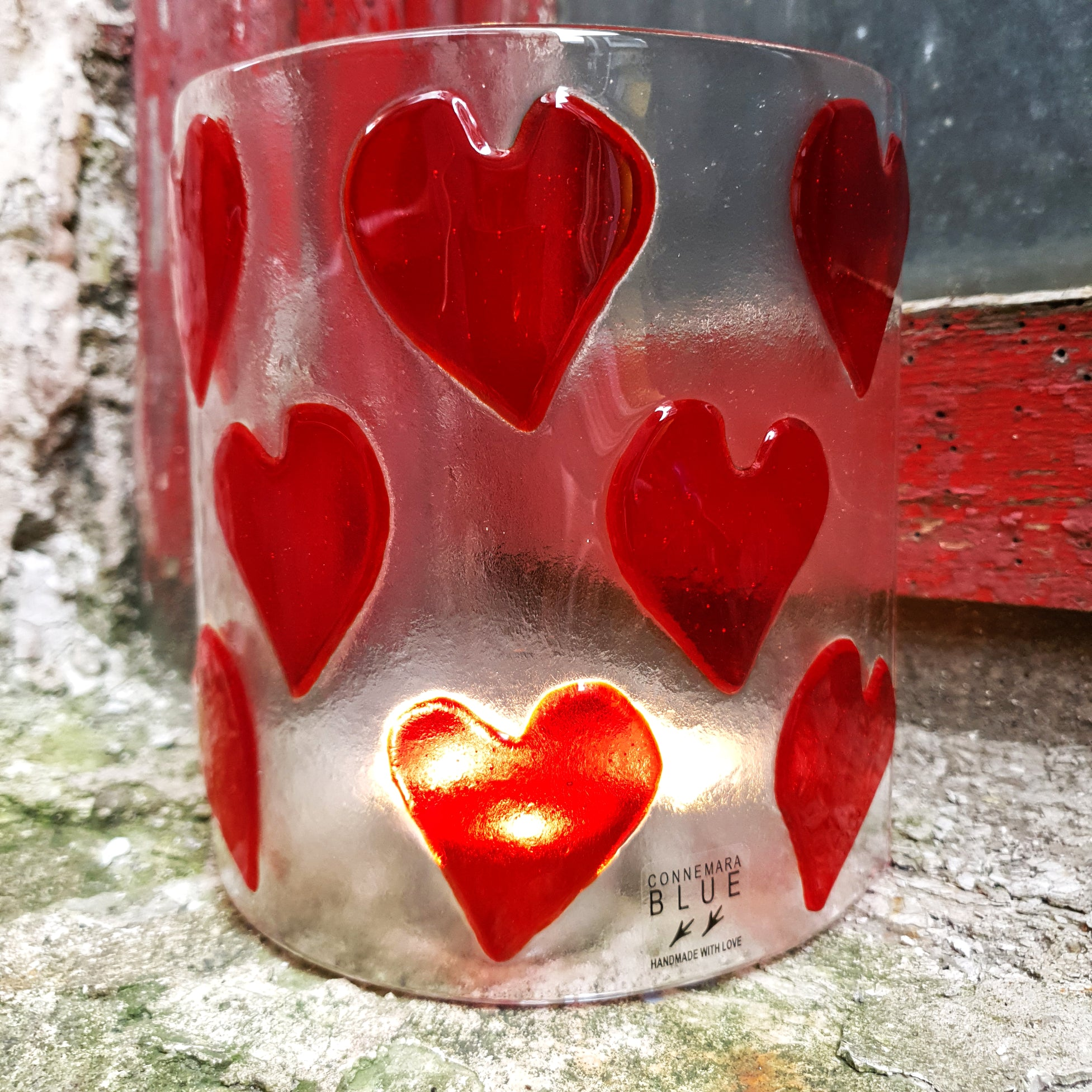 A clear glass candle shield with eight large red hearts, handmade by Connemara Blue