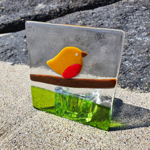 A glass tealight holder featuring a robin on a branch, handmade by Connemara Blue