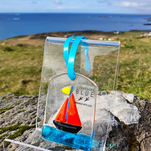 A fused glass decoration featuring a bright sailboat on the ocean, handmade by Connemara Blue