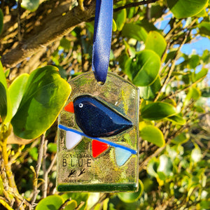A fused glass decoration featuring a sparkly blue bird on bunting, handmade by Connemara Blue