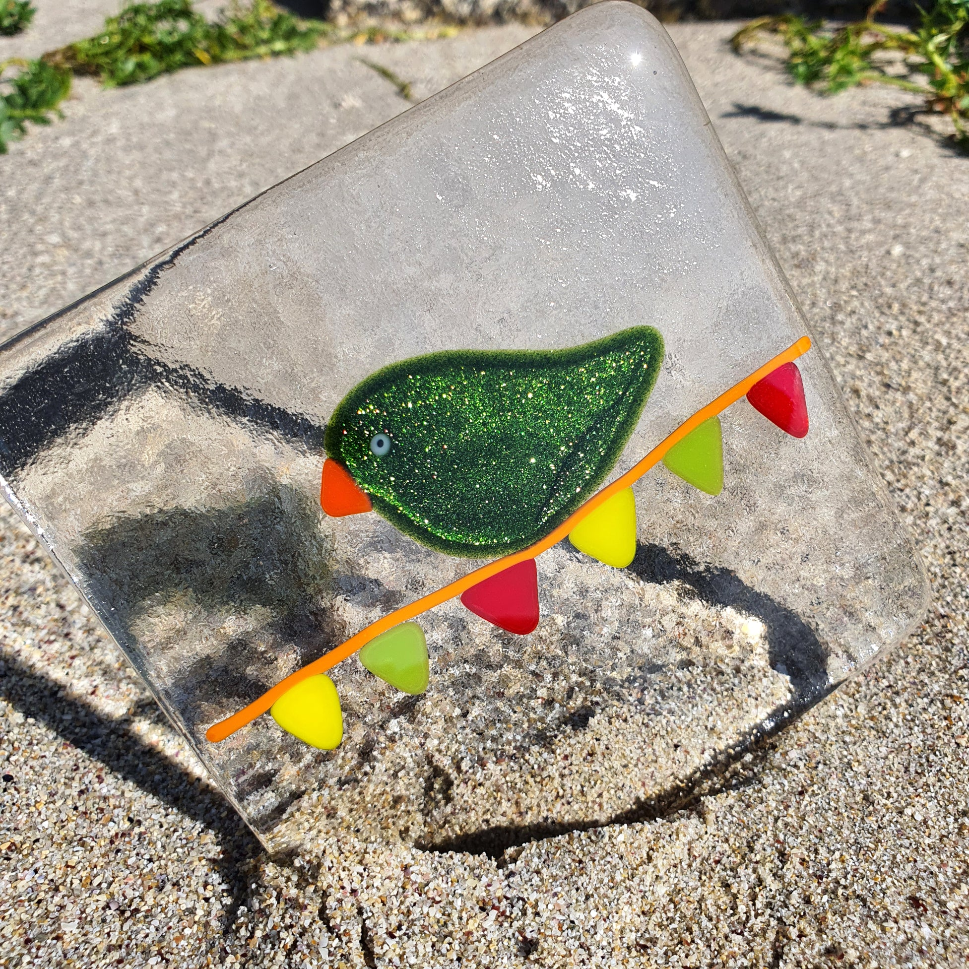 A unique clear glass coaster featuring a sparkly green bird on carnival bunting. Handmade by Connemara Blue.