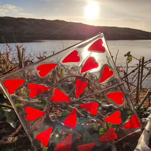 A beautiful clear glass plate featuring 20 red hearts. Perfect for pillar candles or preserve or condiment jars. Handmade by Connemara Blue