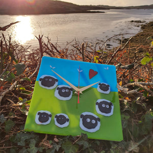 A square fused glass clock featuring sheep and lambs in a green field, with blue sky, birds and a red heart. Handmade by Connemara Blue