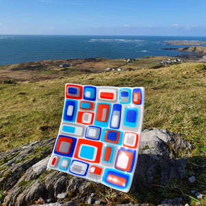 A fused glass square plate in stacks of blue, red, grey and white layers, handmade by Connemara Blue