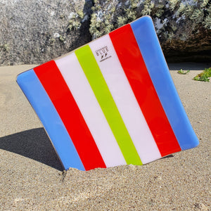 A square fused glass plate in stripes of periwinkle, red, pink and spring green opal glass. Handmade by Connemara Blue